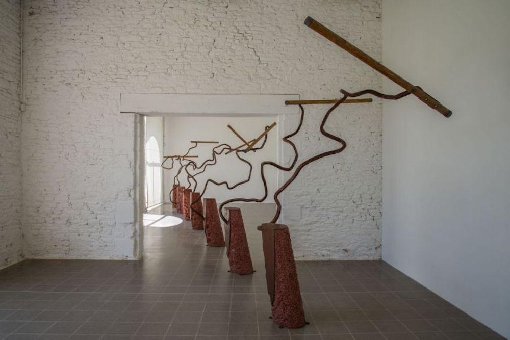Bernard Pagès, Fléaux, 1994, ensemble de sept sculpture béton coloré, tôle, acier torsadé et oxydé, bois de châtaigner, 285 x 1250 x 310 cm. Photo Domaine de Kerguéhennec