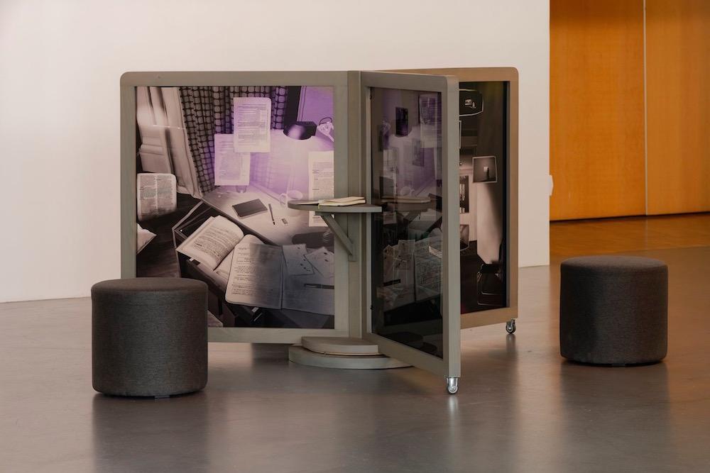 Sébastien Rémy, «Tant que je vous parle ce n'est pas une frontière», depuis 2017. Structure en bois, impression sur Plexiglas, assises, carnets, conversations a durées variables, 121 × 213 cm (H × O). Co-production : CAC Bretigny et La Galerie, centre d'art contemporain de Noisy-le-Sec (2017). Ce projet a été sélectionné par la commission mécénat de la Fondation des Artistes (2015) qui lui a apporté son soutien. Vue de l'exposition «les cellules blanches, nues et le sommeil électrique» (co. Céline Poulin, assistée de Camille Martin), CAC Brétigny, 2019. Photo: Aurélien Mole