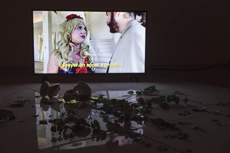 Vue de l'exposition « UN MAXIMUM DE… » (octobre 2019), installation vidéo, plaque de pvc effet marbre, vase, fleur, mobile en perle. Eglise st Nicolas, Caen