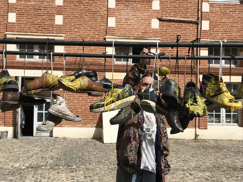 Carla Lloret Palmero, Stand de cirage de pompes, 2021. Cire, paires de chaussures. 350x70x170cm Photographie lors de la performance.